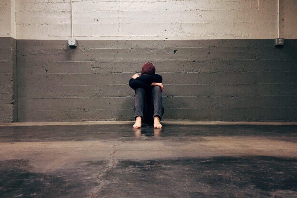 Bullismo: vediamo un ragazzo scalzo, con il cappello, seduto a terra con il volto nascosto da braccia e gambe.