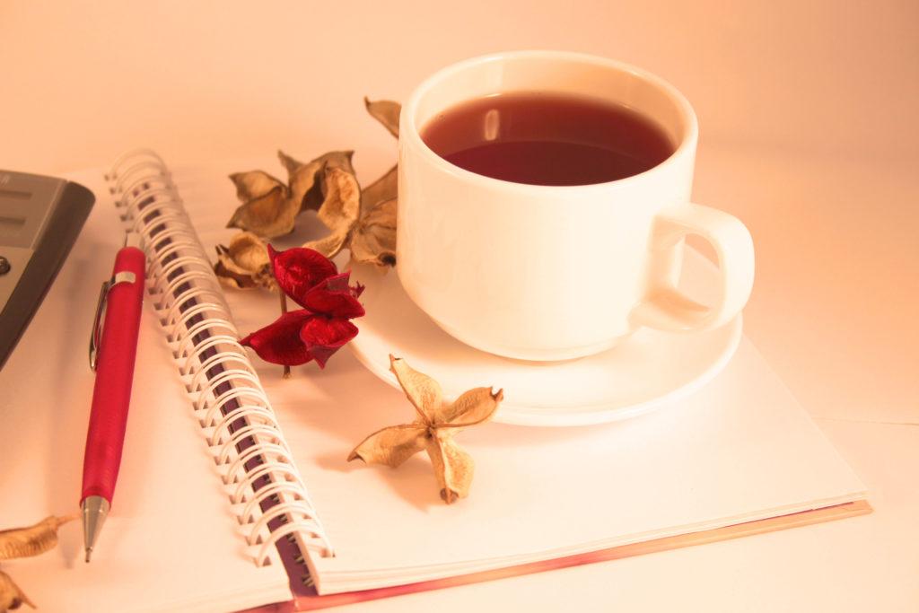 Una calcolatrice, una matita, un blocco per gli appunti, una tazza di té e dei fori secchi rossi e gialli.